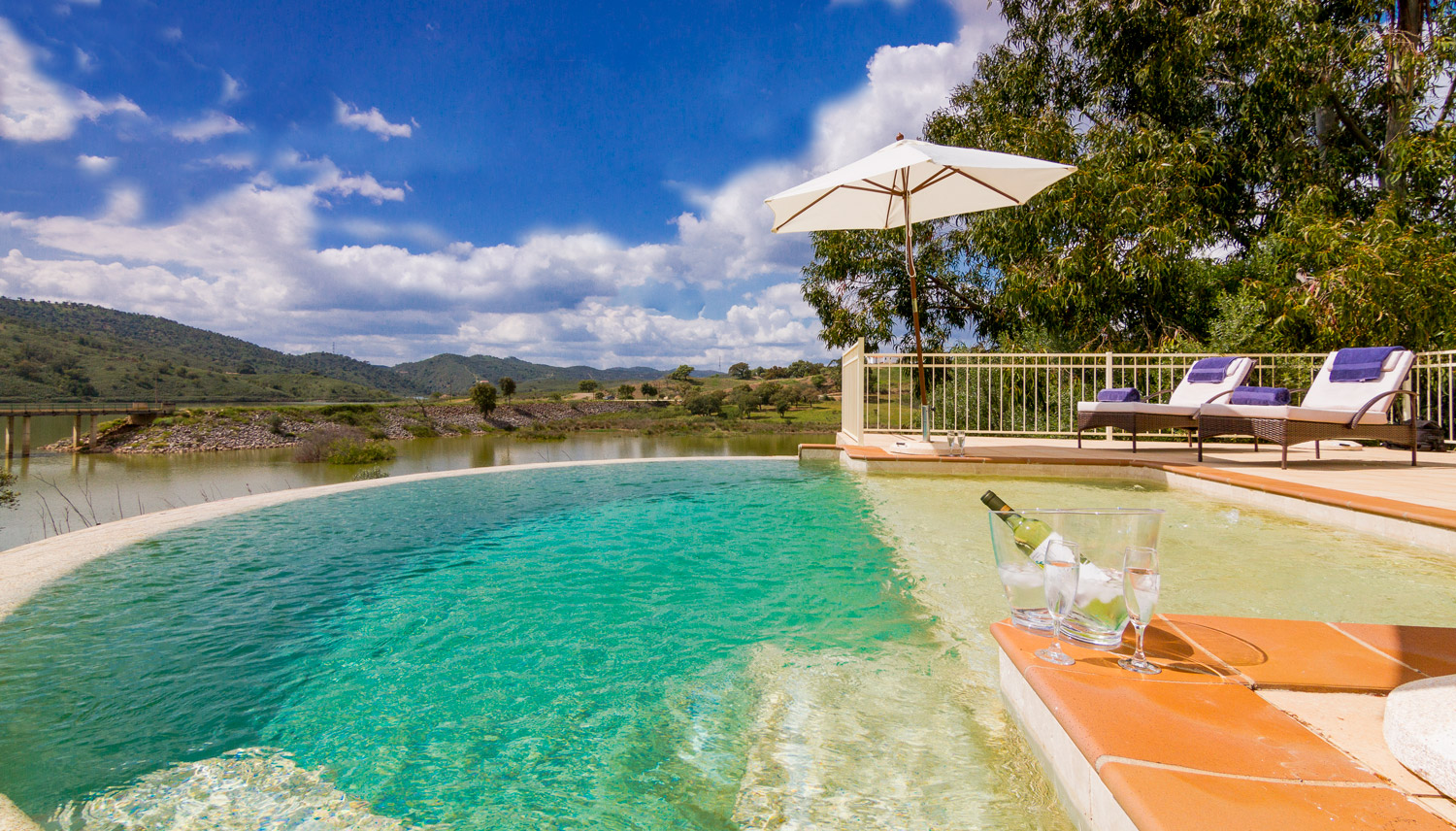 Infinity pool overlooking the river with views of the mountains, Algarve, Portugal