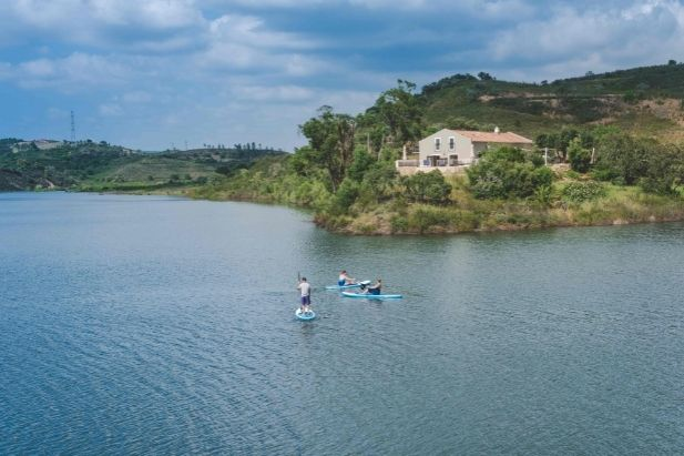 paddle boarders on river with villa behind